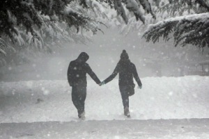 A couple walk during a snowfall in an amusement park in Tbilisi